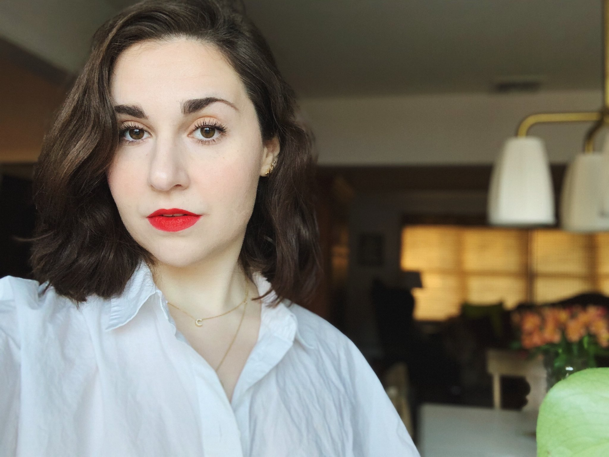 Woman with dark wavy hair and red lipstick looking at the camera