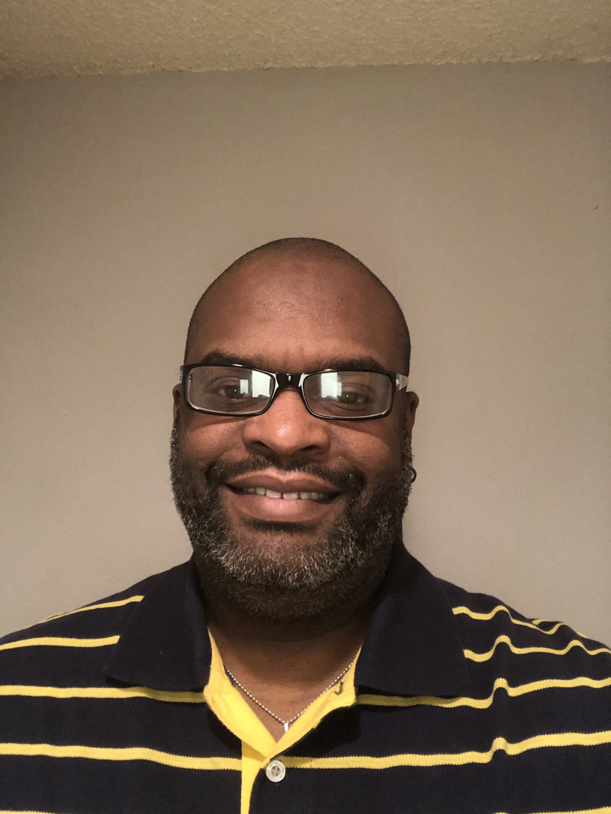 Closeup picture of black man smiling wtih glasses and black and yellow striped polo shirt
