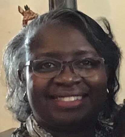 Closeup picture of black woman smiling with glasses and grey hair