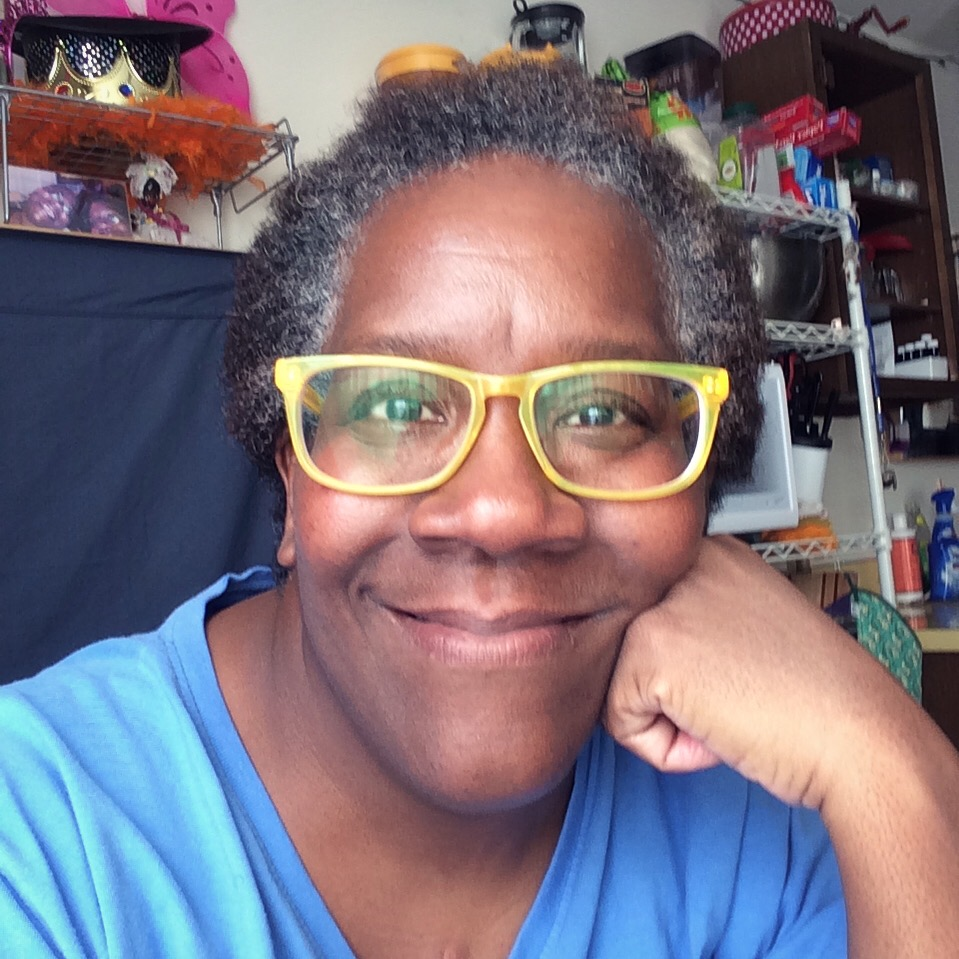 Closeup picture of black woman smiling with blue shirt and yellow glasses