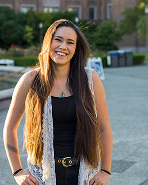 Photo of person with long golden brown hair wearing a white lace shirt and black tank top, smiling at camera